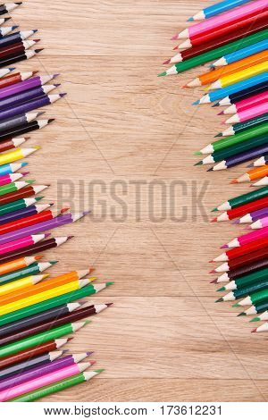 Different colored pencils opposed each other, on a wooden background. Brown table. Place for the text. Art and design. School nad education.