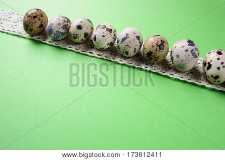 Quail eggs with ribbon on the green background
