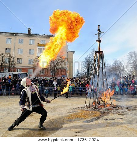 Orel Russia - February 26 2017: Maslenitsa fest. Man breathing fire in fire show at burnt Lady Maslenitsa on square