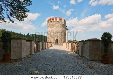 Well restored tower gate beyonf the bridge in classic european castle