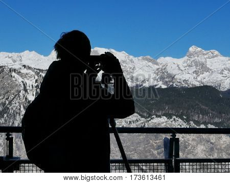 Silhouette of male landscape photographer capturing breathtaking view of snow capped mountain range