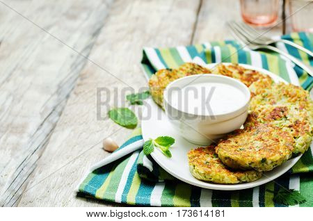 Cauliflower sweet potato Fritters with greek yogurt mint sauce on a wood background.