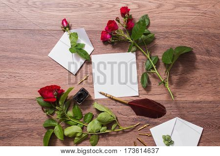 Fountain pen and ink on wooden background. White envelope and red roses. Greeting card. Conceptual photography. Wedding invitation card with roses. Valentine day. Tips to pen. Flat lay roses copyspace mock up