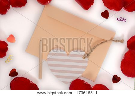 Light apricot envelope, heart card and pencil on white and rose petals background. For Happy Women Day or Valentines