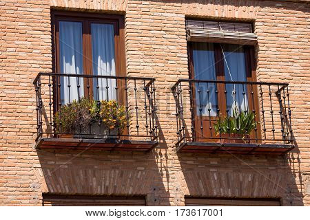 Traditional European house facade with balconys with colorful flowers and blinds