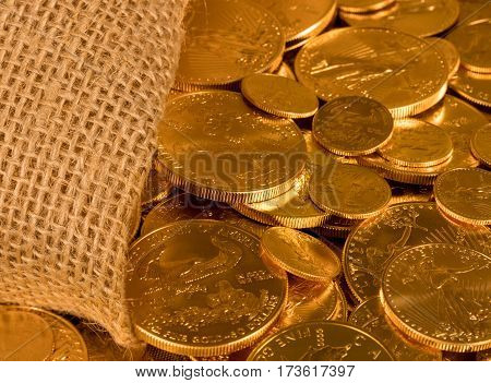 Gold Eagle one ounce coins being poured out of a woven sacking bag suggesting immense wealth