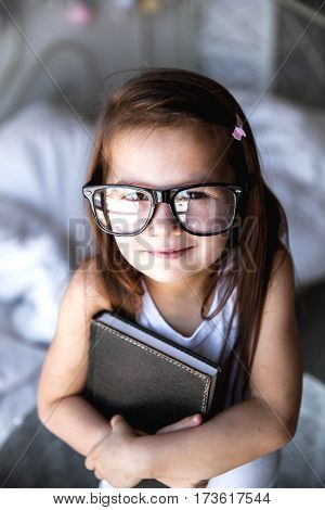 Preschooler girl with book and glasses. teaching student education