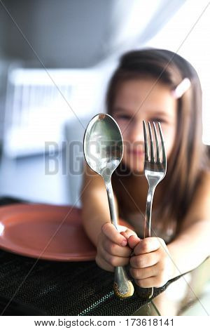 Beautiful Asian girl holding a spoon and fork with empty white plate in restaurant