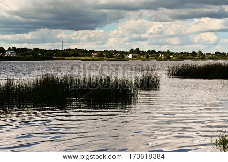 beautiful landscape with a lake on the other side there are small houses, calm water, cloudy, evening, in water, scraps of vegetation, summer, processed, skyline