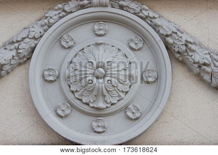 Round architectural element with flowers on the wall of  building