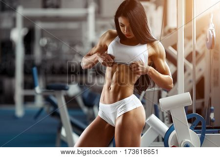Fitness woman showing abdominal muscles. Bodybuilder motivation. Perfect female sports figure. Fitness woman posing in the gym. Fitness photo shoot in the gym. Fitness bikini