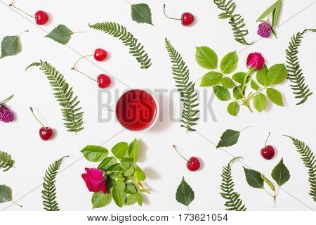 Compote of cherry. Red tea in a cup green blades of grass with purple flowers leaves birch twigs rose with red flowers green ferns ripe cherries lie on a white background. Flat lay top view. Herbal  compote