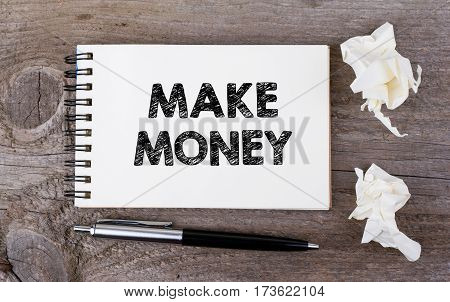 Make Money. On a wooden table notebook and pen.