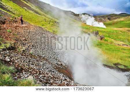 Woman Hiking On Trail In Beautiful Geothermal Landscape Along Geysers In Hveravellir, Iceland
