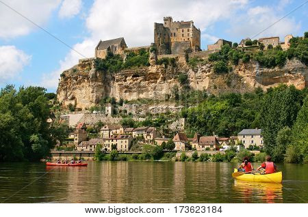Beautiful Landscape With Tourists Kayaking On River Dordogne And Château De Beynac In The Background