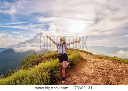 Happy hiker cute teen girl with dslr camera cap eyeglass and backpack stand smiling open arms on peak mountain and sky during sunset background at Phu Chi Fa Forest Park Chiang Rai Thailand