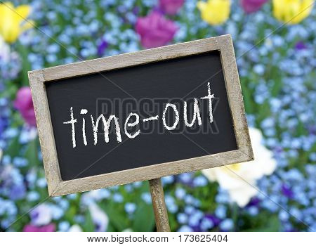 time-out - chalkboard with text and flowers in the background
