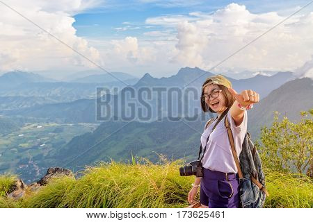 Happy hiker asian cute teen girl with dslr camera cap eyeglass and backpack stand smiling poses thumb up on top of mountain at viewpoint Phu Chi Fa Forest Park in winter Chiang Rai Thailand