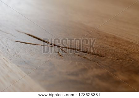 Closeup of crack in wooden table top made of oak wood. Shallow depth of field.