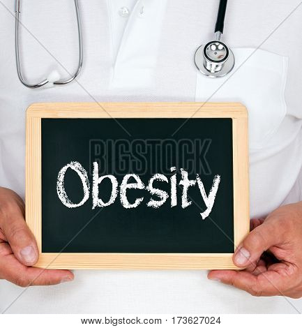Obesity - Doctor holding chalkboard with text