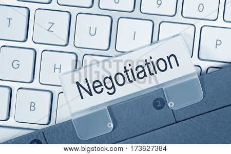 Negotiation - folder with text on computer keyboard