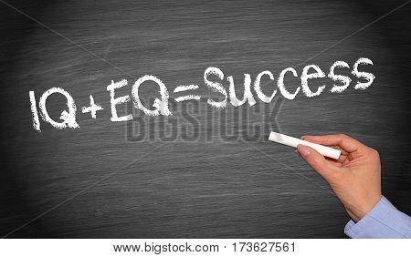 IQ plus EQ = Success - female hand writing text on chalkboard