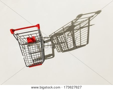 Empty shopping cart on white with a strong shadow