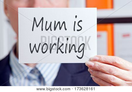 Mum is working - Businesswoman with sign in the office