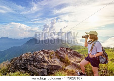 Hiker asian teen girl wear cap and eyeglass with happy holding dslr camera shooting photo beautiful nature in winter on peak mountain at sunset in Phu Chi Fa Forest Park Chiang Rai Thailand