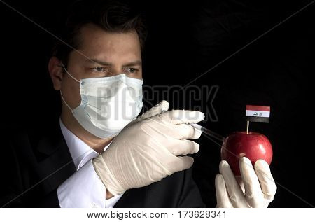Young Businessman Injecting Chemicals Into An Apple With Iraqi Flag On Black Background