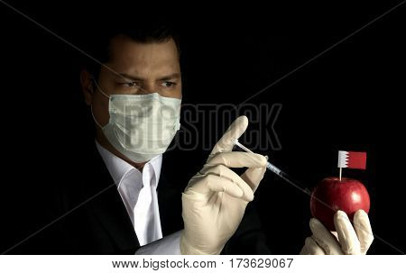 Young Businessman Injecting Chemicals Into An Apple With Bahraini Flag On Black Background