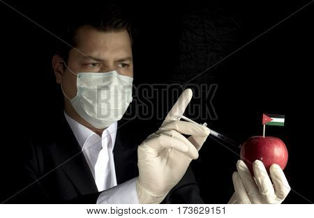 Young Businessman Injecting Chemicals Into An Apple With Jordanian Flag On Black Background