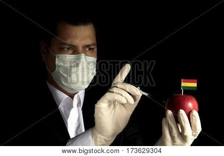 Young Businessman Injecting Chemicals Into An Apple With Bolivian Flag On Black Background