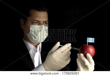 Young Businessman Injecting Chemicals Into An Apple With Guatemalan Flag On Black Background