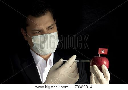 Young Businessman Injecting Chemicals Into An Apple With Tunisian Flag On Black Background
