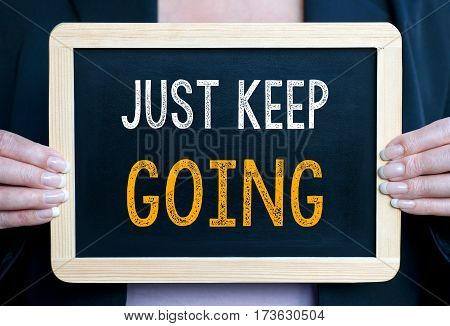 Just keep going - Woman holding chalkboard with text
