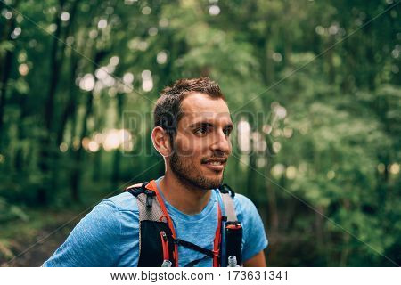Portait of a competitive, athletic millennial man pauses before running off road outdoors through the woods on a trail in the afternoon wearing sportswear.