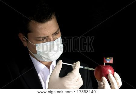 Young Businessman Injecting Chemicals Into An Apple With Antigua And Barbuda Flag On Black Backgroun