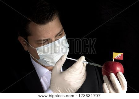 Young Businessman Injecting Chemicals Into An Apple With Bhutanese Flag On Black Background