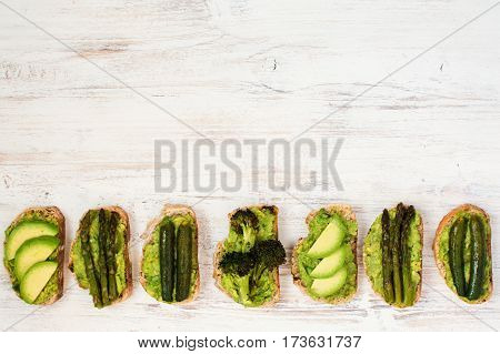 Green vegetarian sandwiches selection made with avocado courgette asparagus broccoli top view copy space