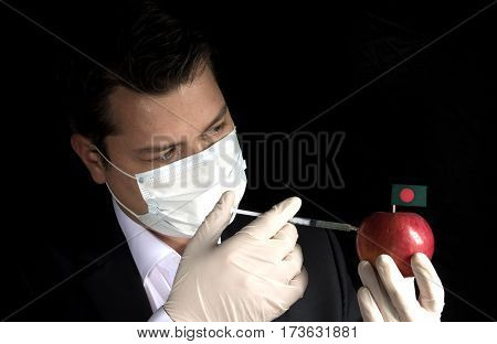 Young Businessman Injecting Chemicals Into An Apple With Bangladeshi Flag On Black Background