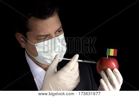 Young Businessman Injecting Chemicals Into An Apple With Malian Flag On Black Background