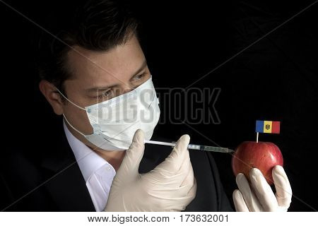 Young Businessman Injecting Chemicals Into An Apple With Moldovan Flag On Black Background