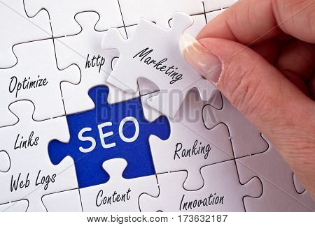 SEO - Search Engine Optimization - puzzle with text and female hand