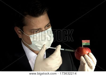 Young Businessman Injecting Chemicals Into An Apple With Burkina Faso Flag On Black Background