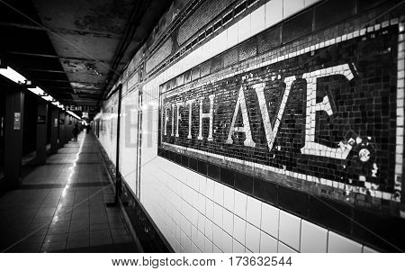 Black and white image of the Fifth Avenue Subway Station in Manhattan with mosaic sign