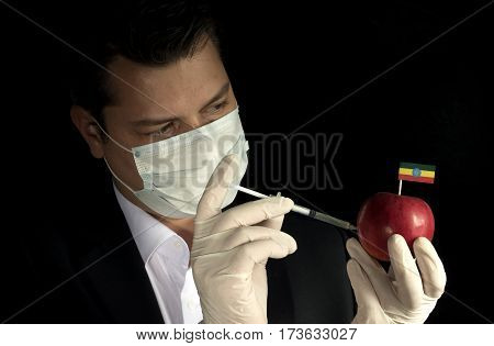 Young Businessman Injecting Chemicals Into An Apple With Ethiopian Flag On Black Background