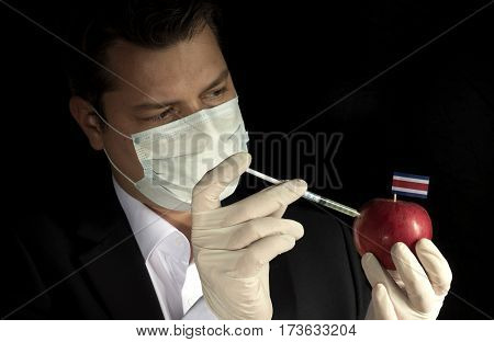 Young Businessman Injecting Chemicals Into An Apple With Costa Rican Flag On Black Background