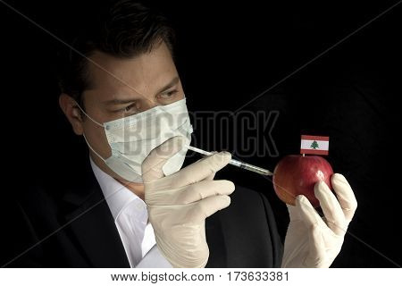 Young Businessman Injecting Chemicals Into An Apple With Lebanese Flag On Black Background