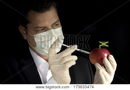 Young Businessman Injecting Chemicals Into An Apple With Jamaican Flag On Black Background